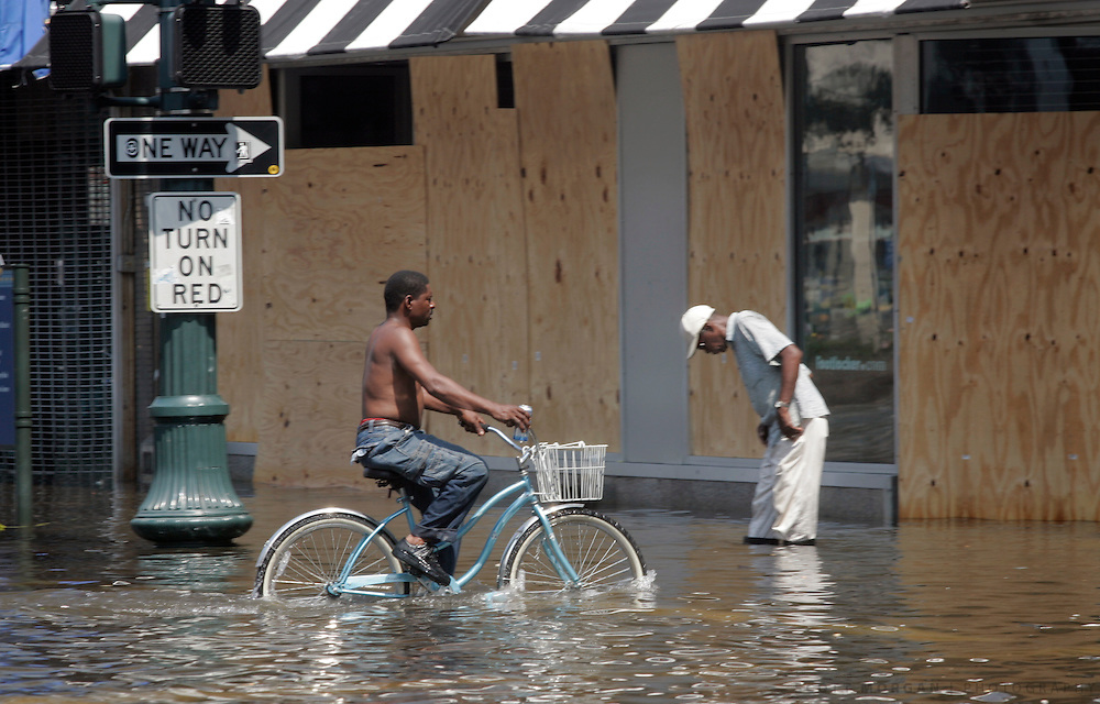 A man rides his bicycle through water on Canal Street Wednesday, August 31, 2005, in New Orleans, La. Scott Morgan