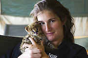 Serval<br /> Felis serval<br /> Suzi Eszterhas (Photographer/foster mom) with 2.5 week old orphan kitten<br /> Tanzania