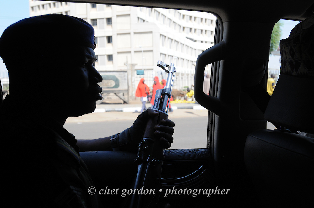 A Nigerian policeman views pedestrians and motorists from the backseat of an escort vehicle in Kano, Nigeria on Tuesday, December 4, 2012. A police officer directing traffic was killed when a roadside bomb exploded near his intersection in Kano the day before.