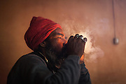 An India Sadu smoking Charras from a chillum, Lucknow, UP.