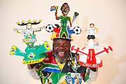 Alfred 'Lux' Baloyi the originator behind the design of the Makarapa poses for photographs at his Makarapa factory in Northern Johannesburg. The Makarapa is a hand painted and sculptured builders hard hat modified by South African football fans to include the team colours, slogans and heroes..Bayoli started making Makarapa's in the 1970's as head protection after a fan was hit on the head with a missile at a football match. The design soon developed into an essential fan article and work of art with unique paintings and craftwork. The term Makarapa goes back to the 1970's and early 80's and means migrant worker, the association being the helmets worn by immigrant workers in the mines around Johannesburg. Today the term is synonymous with the decorated and elaborate hard hat. Alfred's factory is working flat out in the run up to the world cup and employs approximately 25 staff. Orders have been placed by large multinationals for advertising campaigns and by individuals looking for a personalised world cup souvenir. www.makarapa.co.za ...Pictures © Zute & Demelza Lightfoot. www.lightfootphoto.com, zutelightfoot@yahoo.co.uk