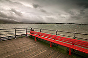 Bright red bench atthe end of the pier in Beaumaris, Anglesey, with stormy winter weather over the Welsh mountains of Snowdonia and tje wind swept Menai Strait in the middle & far distance. The pier has been altered since this image to take a floating pontoon