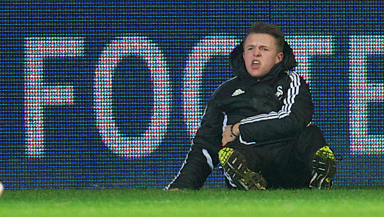 SWANSEA, WALES - Wednesday, January 23, 2013: Swansea City ball-boy Charlie Morgan lies injured on the ground after being kicked by Chelsea's Eden Hazard during the Football League Cup Semi-Final 2nd Leg match at the Liberty Stadium. (Pic by David Rawcliffe/Propaganda)