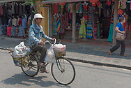 Hoi An, Vietnam--March 23, 2016. A man rides his bicycle past stores on a busy shopping street in   Hoi An Vietnam.