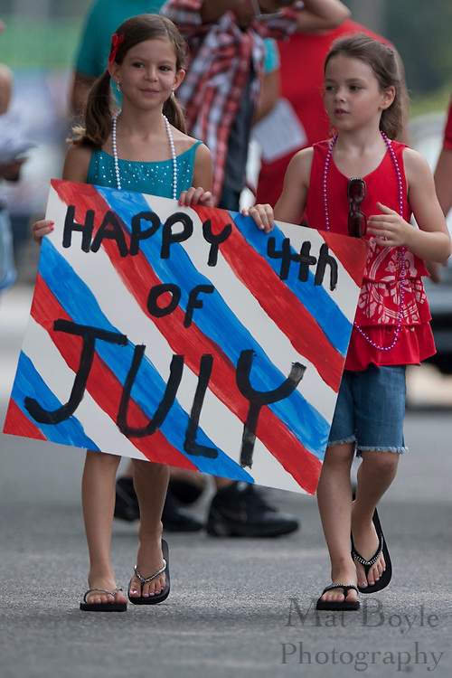 Girls carry a Happy 4th of July Sign in Ptman's 4th of July Parade.