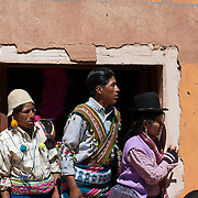 Villagers watch from a doorway as rival villages fight in the streets of Macha during the Tinku Festival. Macha, Bolivia, 4th May 2010, Photo Tim Clayton ..Each May, up to 3000 thousands indigenous Bolivian indians descend on the isolated mountainous village of Macha 75 miles north of Potosi in the Bolivian Andes. The 600 year old pre-hispanic Bolivia Festival of Tinku sees villagers from all over the region march into town to be pitted against each other in a toe to toe fist to fist combat.. They dance and sing in traditional costume and drink 96% proof alcohol along with chicha, a fermented beverage made from corn. Townspeople and sometimes the police oversee proceedings who often use tear gas to try and control the villages, whipped into a fighting frenzy by the dancing and alcohol, but as the fiesta goes on things often escalate beyond their control, with pitched battles between rival villages break out,  The blood spilt is an offering to the earth goddess - Pachamama - to ensure a good harvest for the coming year. Over the years dozens have died, yet the rite continues.