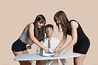Young women ironing shocked man's tie over colored background