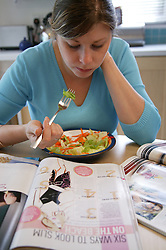 Young woman eating a low calorie lunch and reading a dieting magazine,