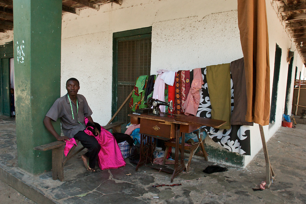 Entrepreneur sets up his sewing machine on the porch of a large multi-family residence in Tanga, Tanzania.