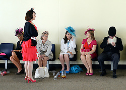 © Licensed to London News Pictures. 21/06/2012. Ascot, UK Racegoers shelter front he rain. Ladies Day at Royal Ascot 21st June 2012. Royal Ascot has established itself as a national institution and the centrepiece of the British social calendar as well as being a stage for the best racehorses in the world.. Photo credit : Stephen Simpson/LNP