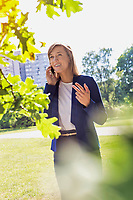 Portrait of young attractive businesswoman talking on smartphone in park