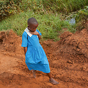 CAPTION: Juliet walks to school along a dirt road, barefoot. Her destination is not too far from her home, only a kilometre or two; many of her classmates have to walk far greater distances for their education. The lack of shoes can lead to hygiene issues, because families frequently sleep on the same floors on which they walk, leading in turn to objects becoming lodged in the ear and to ear infections. LOCATION: Butenga Village, near Masaka City, Bukomansimbi District, Central Region, Uganda. INDIVIDUAL(S) PHOTOGRAPHED: Juliet Nassuna.