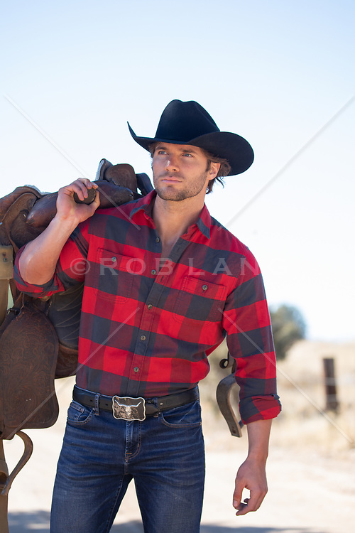 good looking cowboy with a saddle outdoors