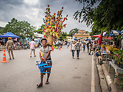 "12 JULY 2014 - PHRA PHUTTHABAT, SARABURI, THAILAND: A toy vendor walks down the street before the Tak Bat Dok Mai at Wat Phra Phutthabat in Saraburi province of Thailand. Wat Phra Phutthabat is famous for the way it marks the beginning of Vassa, the three-month annual retreat observed by Theravada monks and nuns. The temple is highly revered in Thailand because it houses a footstep of the Buddha. On the first day of Vassa (or Buddhist Lent) people come to the temple to ""make merit"" and present the monks there with dancing lady ginger flowers, which only bloom in the weeks leading up Vassa. They also present monks with candles and wash their feet. During Vassa, monks and nuns remain inside monasteries and temple grounds, devoting their time to intensive meditation and study. Laypeople support the monks by bringing food, candles and other offerings to temples. Laypeople also often observe Vassa by giving up something, such as smoking or eating meat. For this reason, westerners sometimes call Vassa ""Buddhist Lent.""    PHOTO BY JACK KURTZ"