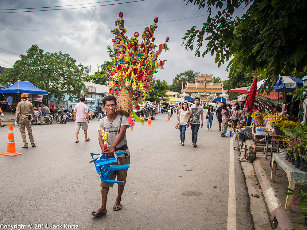 """12 JULY 2014 - PHRA PHUTTHABAT, SARABURI, THAILAND: A toy vendor walks down the street before the Tak Bat Dok Mai at Wat Phra Phutthabat in Saraburi province of Thailand. Wat Phra Phutthabat is famous for the way it marks the beginning of Vassa, the three-month annual retreat observed by Theravada monks and nuns. The temple is highly revered in Thailand because it houses a footstep of the Buddha. On the first day of Vassa (or Buddhist Lent) people come to the temple to """"make merit"""" and present the monks there with dancing lady ginger flowers, which only bloom in the weeks leading up Vassa. They also present monks with candles and wash their feet. During Vassa, monks and nuns remain inside monasteries and temple grounds, devoting their time to intensive meditation and study. Laypeople support the monks by bringing food, candles and other offerings to temples. Laypeople also often observe Vassa by giving up something, such as smoking or eating meat. For this reason, westerners sometimes call Vassa """"Buddhist Lent.""""    PHOTO BY JACK KURTZ"""