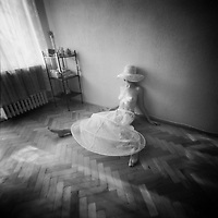 A half naked young woman wearing a floppy straw hat sitting on a pargued floor in an empty room
