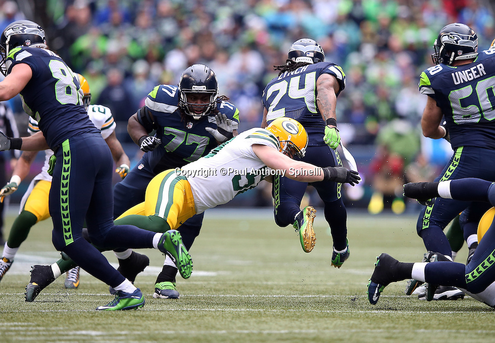 Seattle Seahawks running back Marshawn Lynch (24) leaps away from a diving tackle attempt by Green Bay Packers inside linebacker A.J. Hawk (50) during the NFL week 20 NFC Championship football game against the Green Bay Packers on Sunday, Jan. 18, 2015 in Seattle. The Seahawks won the game 28-22 in overtime. ©Paul Anthony Spinelli