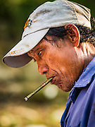 04 NOVEMBER 2015 - YANGON, MYANMAR: A worker with a cheroot clenched in his mouth repairs the hull of a small wooden ferry on the banks of the Yangon River in Dala. Dala is located on the southern bank of Yangon River across from downtown Yangon, Myanmar. Many Burmese live in Dala and surrounding communities and go across the river into central Yangon for work. Before World War 2, the Irrawaddy Flotilla Company had its main shipyards in Dala. That tradition lives on in the small repair businesses the work on the hundreds of small wooden boats that serve as commuter ferries for the people of Yangon. The boats are pulled up onto the riverbank in Dala and repaired by hand.    PHOTO BY JACK KURTZ