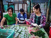 23 NOVEMBER 2017 - YANGON, MYANMAR: Women make packets of betel they sell to workers in the San Pya Fish Market. Betel is a mild stimulant rolled with betel nut, tobacco and other additives inside betel leaf. It used to chewed throughout Southeast Asia and India but health campaigns have seen betel use greatly reduced in most places besides Myanmar.  San Pya Fish Market is one of the largest fish markets in Yangon. It's a 24 hour market, but busiest early in the morning. Most of the fish in the market is wild caught but aquaculture is expanding in Myanmar and more farmed fresh water fish is being sold now than in the past.    PHOTO BY JACK KURTZ