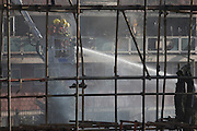 London Fire fighters dampen down smouldering remains from a Simon Snorkel platform after an inner-city estate fire in south London. About 310 people were forced to leave their homes after the fire engulfed a wooden structure under construction in scaffolding at Sumner Road and Garrisbrooke Estate, Peckham, London at about 0430 AM. It spread to two blocks of maisonettes and a destroyed a pub. More than 150 firefighters tackled this unusually large and ferocious fire which injured ten people, including two police officers who received hospital treatment for minor injuries.  .