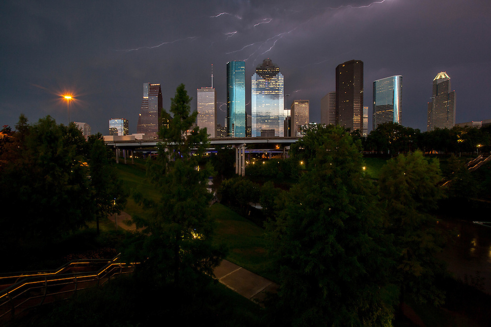 Lightning in stormy night sky over Houston, Texas skyline Buffalo Bayou in foreground.