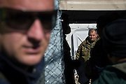 March 5, 2016 - Idomeni, Greece: Macedonian soldier waits for refugee who   crosses the border. Make shift camp at the  Idomeni border crossing in Greece. 13,000 refugees are stuck here after Macedonia closed the border. New arrivals come in every day, making living conditions more and more difficult, so that the local government asked the emercency state was declared . (Steven Wassenaar/Polaris)
