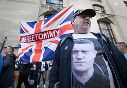 © Licensed to London News Pictures . 27/09/2018. London, UK. A protestors wears a t-shirt with a photograph of former EDL leader Tommy Robinson (real name Stephen Yaxley-Lennon ) outside the Old Bailey, where he faces a retrial for Contempt of Court following his actions outside Leeds Crown Court in May 2018 . Robinson was already serving a suspended sentence for the same offence when convicted in May and served time in jail as a consequence , but the newer conviction was quashed by the Court of Appeal and a retrial ordered . Photo credit: Peter Macdiarmid/LNP