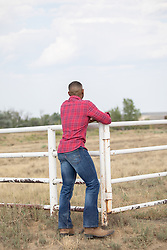 back of a man leaning on a rustic fence