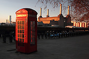 "The January sun rises over south-west London, illuminating ann iconic red telephone box and Battersea Power Station in the background. Inbetween is a row of the London ""Bozza"" bikes."