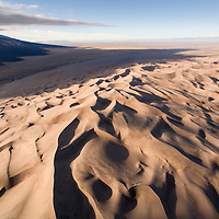 USA, Colorado, Great Sand Dunes National Park, Aerial view of morning sun lighting sand dunes in San Luis Valley