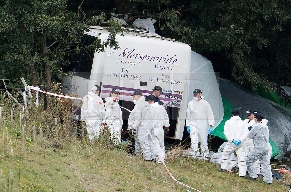 © London News Pictures. 11/09/2012. Hindhead, UK . Forensics  outside the bus. The scene of a fatal bus crash on the north bound A3 motorway near Hindhead Tunnel, Hindhead, Surrey on September 11, 2012.Three people were killed and a number of others seriously injured when a coach carrying overturned after crashing into a tree. Photo credit: Ben Cawthra/LNP