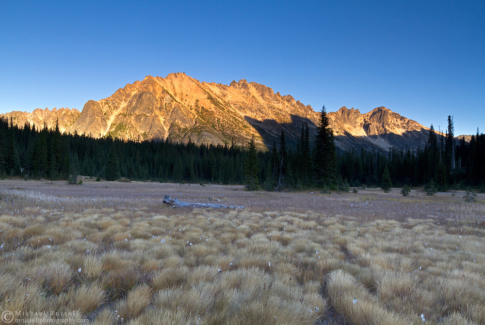 The shadow of the Early Winter Spires creep up Kangaroo Ridge from the meadows at Washington Pass after sunset - in the North Cascades of the Okanogan-Wenatchee National Forest in Washington State, USA.