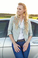 Beautiful young woman looking away while standing by car at countryside