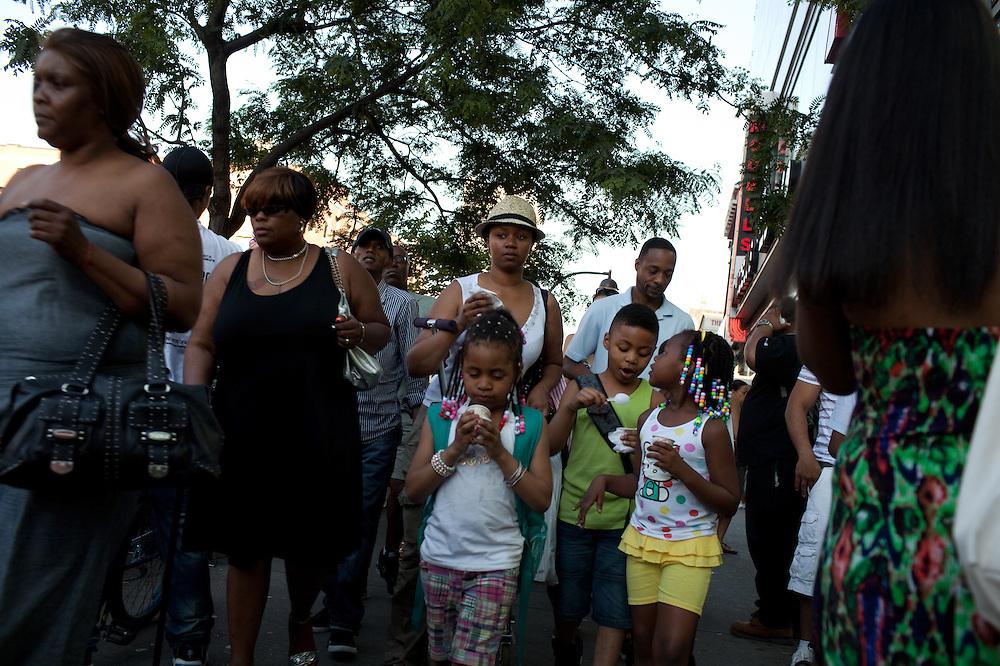 Walking along 125th Street in Harlem, New York on June 22, 2012.