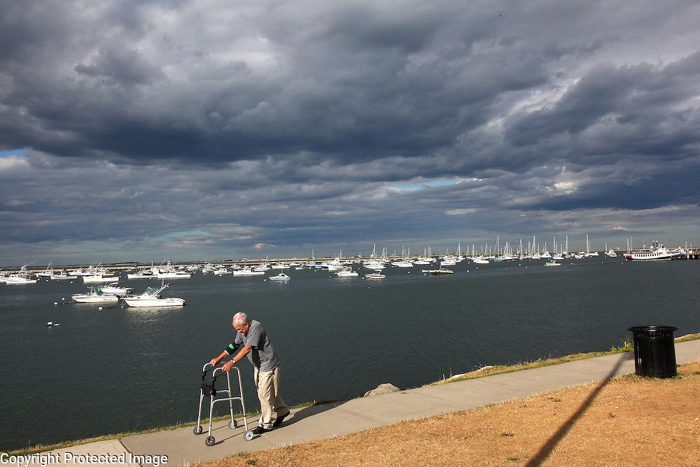 A man with a walker passes by Plymouth Harbor's privately owned boats in Plymouth, Mass. Once a busy fishing port, Plymouth Harbor now caters mostly to tourists and local boat owners.