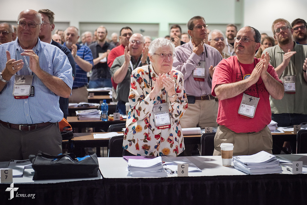 Voting Delegates (L-R) Terry O'Brien of Central Illinois District, Ruth Sweitzer of Pacific Southwest District and Mike Belinsky of Michigan District stand to recognize the Rev. Dr. Raymond L. Hartwig for his service on Thursday, July 14, 2016, at the 66th Regular Convention of The Lutheran Church–Missouri Synod, in Milwaukee. LCMS/Frank Kohn
