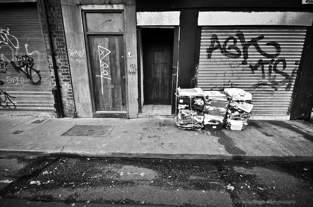 Rubbish piles up beside a doorway amid the dirty graffiti covered side street in Dublin City on a dark and moody afternoon in Ireland's Capital