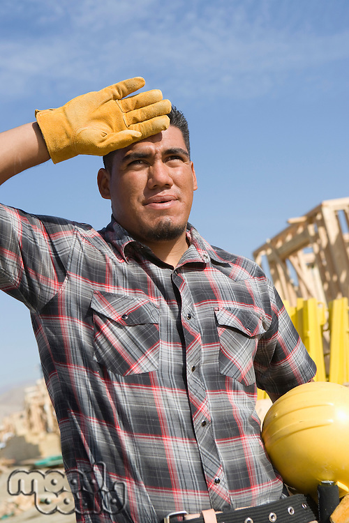Construction worker wiping his forehead with his hand