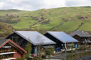 Roofs tiled with photovoltaic solar energy panels receive maximum sunlight exposure in Dyfi Eco Park, Machynlleth, Wales. These panels are made up of photovoltaic (PV) cells. PV cells convert sunlight into electrical energy. Photovoltaic panels are an economical, efficient way to produce electricity.