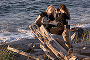 Two friends have fun taking pictures on Ediz Hook in Port Angeles, along the shore of the Strait of Juan de Fuca, late in the summer day.
