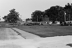 Mid 1970's.  Storm blows over old oak tree at the Baseball field behind the Elementary school - Heyworth IL <br /> <br /> <br /> Archive slide, negative and print scans.