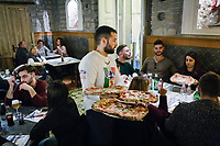 "NAPLES, ITALY - 8 DECEMBER 2017: A waiter serves pizzas to customers here at Pizzeria Gino Sorbillo in Naples, Italy, on December 8th 2017.<br /> <br /> On Thursday December 7th 2017, UNESCO added the art of Neapolitan ""Pizzaiuolo"" to its list of Intangible Cultural Heritage of Humanity.<br /> <br /> The art of the Neapolitan 'Pizzaiuolo' is a culinary practice comprising four different phases relating to the preparation of the dough and its baking in a wood-fired oven, involving a rotatory movement by the baker. The element originates in Naples, the capital of the Campania Region, where about 3,000 Pizzaiuoli now live and perform. Pizzaiuoli are a living link for the communities concerned. There are three primary categories of bearers – the Master Pizzaiuolo, the Pizzaiuolo and the baker – as well as the families in Naples who reproduce the art in their own homes. The element fosters social gatherings and intergenerational exchange, and assumes a character of the spectacular, with the Pizzaiuolo at the centre of their 'bottega' sharing their art.<br /> <br /> In Naples, pizza makers celebrated the victory by giving away free pizzas."