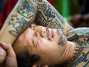 "14 MARCH 2014 - NAKHON CHAI SI, NAKHON PATHOM, THAILAND: A man grimaces as he gets a sak yant tattoo at Wat Bang Phra. Wat Bang Phra is the best known ""Sak Yant"" tattoo temple in Thailand. It's located in Nakhon Pathom province, about 40 miles from Bangkok. The tattoos are given with hollow stainless steel needles and are thought to possess magical powers of protection. The tattoos, which are given by Buddhist monks, are popular with soldiers, policeman and gangsters, people who generally live in harm's way. The tattoo must be activated to remain powerful and the annual Wai Khru Ceremony (tattoo festival) at the temple draws thousands of devotees who come to the temple to activate or renew the tattoos. People go into trance like states and then assume the personality of their tattoo, so people with tiger tattoos assume the personality of a tiger, people with monkey tattoos take on the personality of a monkey and so on. In recent years the tattoo festival has become popular with tourists who make the trip to Nakorn Pathom province to see a side of ""exotic"" Thailand.   PHOTO BY JACK KURTZ"