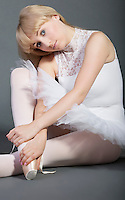 Portrait of young female ballet dancer sitting over grey background