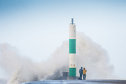 © Licensed to London News Pictures. 13/03/2019. Aberystwyth, UK. Young men take risks to get dramatic photographs of themselves close to the waves as gale force winds from Storm Gareth - the third named storm of 2019 - hit  Aberystwyth on the Cardigan Bay coast, West Wales on Wednesday afternoon. Gusts of up to 70 or 80mph are forecast in exposed Northern regions, with the risk of serious damage to property and severe disruption to travel and power services. Photo credit: Keith Morris/LNP