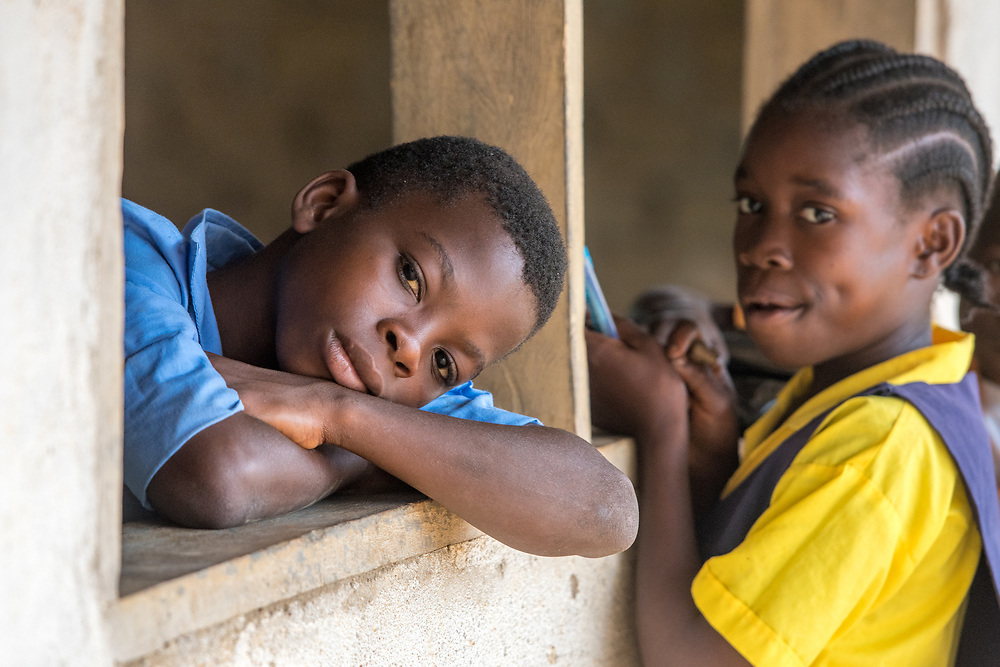Two children rest on windowsills in Ganta, Liberia