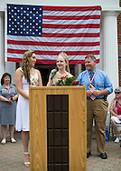 Wantagh, New York, USA. July 4, 2015. KAYLA KNIGHT, Miss Wantagh 2014, looks at newly crowned KERI BALNIS, Miss Wantagh 2015, who is speaking at the podium, and Nassau County Legislator STEVE RHOADS (Rep - Bellmore, LD 19), who announced the 2015 winner, is at right, at The Miss Wantagh Pageant ceremony, a long-time Independence Day tradition on Long Island, held at Wantagh School after the town's July 4th Parade. Since 1956, the Miss Wantagh Pageant, which is not a beauty pageant, crowns a high school student based mainly on academic excellence and community service.