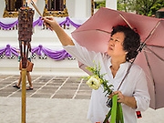 11 JULY 2014 - BANGKOK, THAILAND: A Thai woman lights incense before making merit at Wat Pathum Wanaram for Asalha Puja Day. Asalha Puja is the day the Lord Buddha preached his first sermon to followers after attaining enlightenment. The day is usually celebrated by merit making and listening to a monks' sermons. It is also day before the start of the Rains Retreat, the three month period when monks stay in their temple for intense mediation and spiritual renewal.    PHOTO BY JACK KURTZ