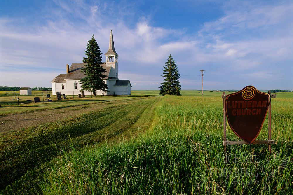 A white country church is accessible by a mowed path through the grass. Rural North Dakota.