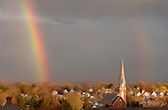 Middletown, N.Y. - A bright rainbow, left, and a fainter rainbow, at right, are visible in the clouds above the steeple of St. Joseph's Church after a spring shower on April 13, 2006.